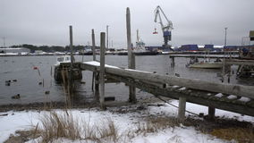 Old wooden jetty, fishing boats, snow and lead-gray water of Baltic Sea. Dolly. stock video