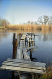 Old wooden jetty at a lake. Landscape with a wooden bridge over the river Stock Photo