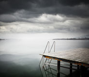 Old wooden jetty on lake. Royalty Free Stock Images