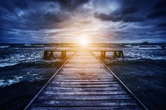 Old wooden jetty during storm on the ocean. Abstract light. At the end. Concept of hope, future, religion, god etc Royalty Free Stock Image