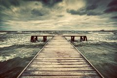 Old wooden jetty during storm on the sea. Dramatic sky with dark, heavy clouds