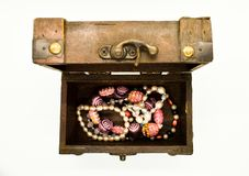 Old wooden jewelry chest from above full of jewelry isolated on white background royalty free stock photo