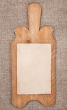 Old wooden kitchen board with aged paper on the burlap Stock Image