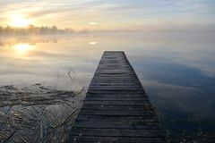 Old wooden lake bridge and autumn morning mist Stock Photos