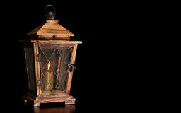 Old wooden lantern with a burning candle isolated on black background. Old wooden lantern with burning candle isolated on black background Stock Images