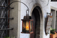 Old wooden lantern with candle near old building Stock Photos