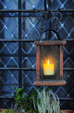 Old wooden lantern with candle near window Royalty Free Stock Images
