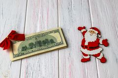 Old wooden light christmas background with a stack of dollars, funny santa figures and a red bow. Gifts for the New Year, holiday stock images