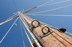 Old wooden mast with crosspieces and backstays, view from deck Stock Image