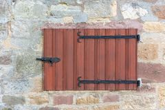 Old wooden medieval window shutters on a stone wall. An old wooden medieval window shutters on a stone wall old wooden medieval window shutters on a stone wall Stock Photo