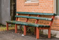 Wooden bench against brick wall Stock Photography