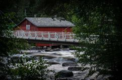 Old wooden mill, Jokela, Findland. Exterior of red painted old mill and footbridge over river in Jokela, Finland Royalty Free Stock Image
