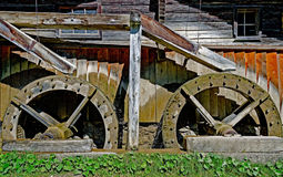Old wooden mill with two overshot waterwheels Royalty Free Stock Photography