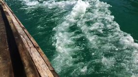 Old Wooden Motor Boat Makes the water into beautiful Waves and Wakes. Slowmotion video HD background. Thailand. stock video footage