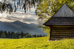 Old wooden mountain chalet and evening mountain ridge Royalty Free Stock Photos