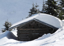 Old wooden mountain hut covered by snow. In austria Stock Photos