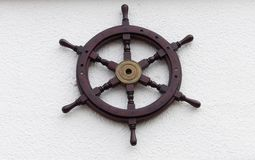 Old wooden naval sailing ship steering wheel. Hanging on a white wall background Stock Photography