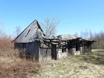 Old not living home in village, Lithuania. Old wooden not living home in village in spring stock photo