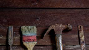 Old wooden with old rusty carpentry tools. Old wooden with rusty carpentry tools; hammer, paint brush, chisel, hacksaw, mortar. horizontal mockup royalty free stock images