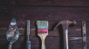 Old wooden with old rusty carpentry tools. Old wooden with rusty carpentry tools; hammer, paint brush, chisel, hacksaw, mortar. horizontal mockup royalty free stock photos
