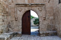 Old wooden open door on a stone wall: a way out of the castle.  Stock Photos