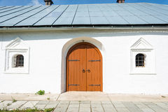 Old wooden orange door in the monastery Church. Stock Images