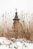 Old wooden orthodox church behind a dry sedge Royalty Free Stock Image