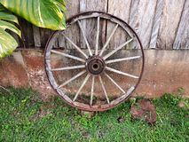 Old wooden ox cart wheel of a farm shed stock image