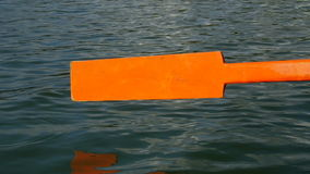 Old wooden paddle bounces into lake water. stock footage