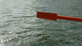 Old wooden paddle bounces into lake water. stock video