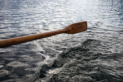 Old wooden paddle over water Stock Images