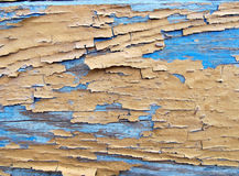 Old wooden painted blue and yellow rustic background. Peeling paint royalty free stock image
