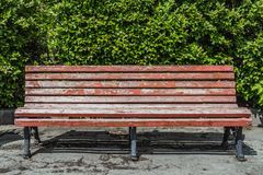 An old wooden painted brown color beautiful bench with black wrought-iron legs is by the walkway in a park on a bush royalty free stock photo