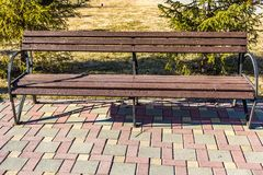 An old wooden painted brown color beautiful bench. With black wrought-iron legs stands by the walkway in a park stock images