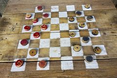 Old Wooden Painted Checkers Board with Red and Black Pieces stock photos