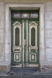 Old wooden painted green doors on street. Old wooden painted green doors in a stone wall with a classical design of columns and grids in the white carved panels Stock Photography