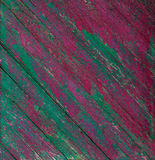 Old wooden painted rustic pink and green fence, paint peeling background. Royalty Free Stock Images