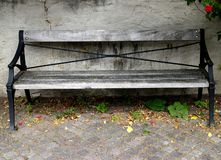 Old wooden park bench stands in front of a weathered stone wall. royalty free stock photos
