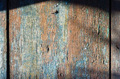 Old wooden  peeling surface shaded top. Old wood surface peeling paint red blue top shadow Royalty Free Stock Image