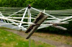 Old wooden pegs on an old and dirty rotary washing line. royalty free stock image