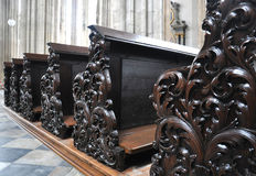 Old wooden pews in a church. Old carved wooden pews in a church Royalty Free Stock Photo