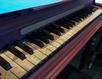 Old wooden piano with notoriously aged keys stock image