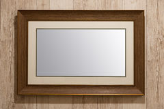 Old wooden picture frame. On wooden wall background Stock Images
