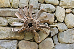 Old wooden piece of watermill mechanism on on a stone wall Royalty Free Stock Photos