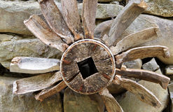 Old wooden piece of watermill mechanism on on a stone wall Stock Photography