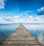 Old wooden pier on big blue lake stock photography