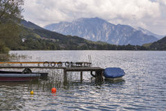 Old wooden pier with boats on Alpine lake Mondsee. Austria stock image