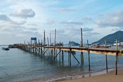 Old wooden pier and boats in the sea Stock Images