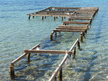old wooden pier extending from the shore into the sea Royalty Free Stock Image