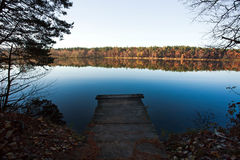 Old wooden pier for fishing in autumn forest lake Stock Images